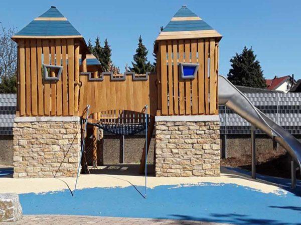 Spielplatzgeräte: Spielturm mit Holzelementen und Rutsche. Spielplatzgeräte für den öffentlichen Raum